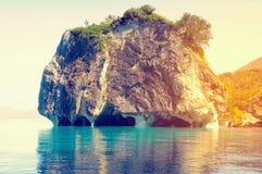 与独特的大理石洞的峭壁在日落 库存照片