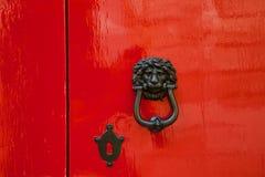 与狮子头金属敲门人的老红色门 库存图片