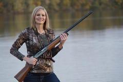 与猎枪的微笑的女性鸭子猎人 图库摄影