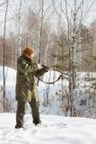 与猎枪的猎人在冬天森林里 图库摄影
