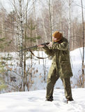 与猎枪的猎人在冬天森林里 库存照片
