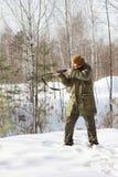 与猎枪的猎人在冬天森林里 免版税库存图片