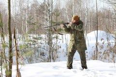 与猎枪的猎人在冬天森林里 免版税图库摄影