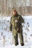 与猎枪的猎人在冬天森林里 库存图片