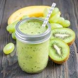 与猕猴桃、绿色葡萄和香蕉的健康圆滑的人在玻璃瓶子,正方形 图库摄影