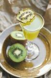 与猕猴桃切片的鸡尾酒在板材的一块玻璃,包装纸背景 绿色饮料,选择聚焦 库存照片