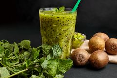 与猕猴桃和薄菏的新鲜的绿色圆滑的人 对一个健康未加工的食物概念的爱 吃健康 免版税库存图片