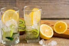 与猕猴桃和薄菏的鸡尾酒在木背景的一块玻璃 选择聚焦 与猕猴桃的自创柠檬水 免版税库存照片