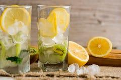 与猕猴桃和薄菏的鸡尾酒在木背景的一块玻璃 选择聚焦 与猕猴桃的自创柠檬水 库存照片
