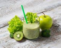 与猕猴桃、苹果、沙拉和硬花甘蓝,健康dri的绿色圆滑的人 库存图片
