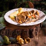 与猪肉大奖章和黄蘑菇调味汁的土豆 免版税库存图片