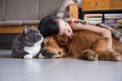 与猫和狗的女孩睡眠 免版税库存照片