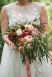 与玉树、玫瑰和异乎寻常的花的美丽的婚礼花束在新娘的手上婚礼礼服的 免版税库存图片