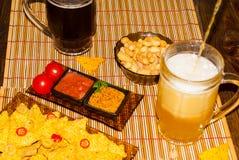 与玉米片蕃茄辣调味汁和芥末的烤干酪辣味玉米片和两块玻璃用在土气木背景的啤酒 纹理背景 警察 库存图片