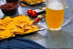 与玉米片蕃茄辣调味汁的烤干酪辣味玉米片、豆和芥末和两块玻璃用啤酒在土气石背景 纹理backgroun 免版税库存图片