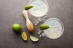 与玛格丽塔酒鸡尾酒的平的位置与石灰、冰块和木剥削者片断在灰色桌面 库存图片