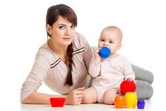 与玩具一起的女婴和母亲作用 库存图片