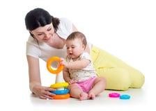 与玩具一起的女婴和妈妈戏剧 库存图片