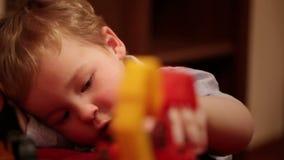 与玩具卡车的两岁的男孩戏剧。 股票视频