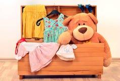 与玩具和女孩衣裳的大胸口 库存照片