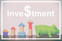 与玩具块上升的图表和存钱罐的投资文本 免版税库存照片