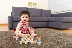 与玩具块的小女孩戏剧 免版税库存图片