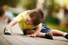 与玩具汽车的小男孩作用 免版税库存照片