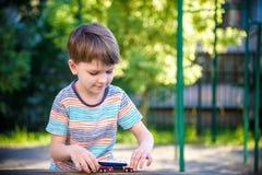 与玩具汽车的男孩戏剧 使用在单独操场的孩子 儿童的白天乐趣 免版税库存图片