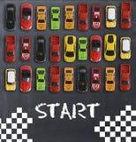 与玩具汽车的种族或竞争概念在黑板 免版税库存图片