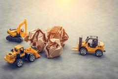 与玩具汽车的被弄皱的纸 库存照片