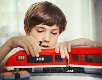 与玩具火车的青春期前的英俊的男孩戏剧 免版税库存照片