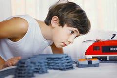 与玩具火车的青春期前的英俊的男孩戏剧 库存图片