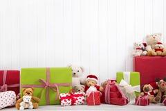 与玩具熊和礼物的白色圣诞节木背景 库存图片