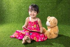 与玩具熊的亚洲中国小女孩阅读书 库存图片