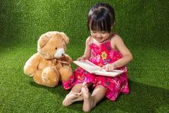与玩具熊的亚洲中国小女孩阅读书 库存照片