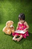 与玩具熊的亚洲中国小女孩阅读书 免版税库存照片