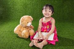 与玩具熊的亚洲中国小女孩阅读书 免版税库存图片