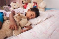 与玩具熊的亚洲男孩睡眠 免版税库存图片