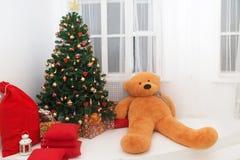 与玩具熊的圣诞树和在木地板上的礼物盒 免版税库存照片