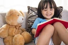与玩具熊的微笑的亚洲中国小女孩阅读书 库存照片