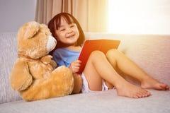 与玩具熊的微笑的亚洲中国小女孩阅读书 免版税库存图片