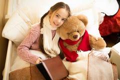 与玩具熊的逗人喜爱的微笑的女孩阅读书在床上 免版税库存照片