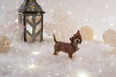 与玩具狗的新年卡片在冬天背景的一个神仙的森林里与雪和光 免版税图库摄影