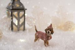 与玩具狗的新年卡片在冬天背景的一个神仙的森林里与雪和光 免版税库存图片