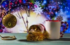 与玩具球、天使和杯子的圣诞节题材反对好的时钟背景的绿色木表面上 图库摄影