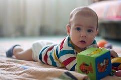 与玩具的一点婴孩戏剧在地板上 免版税库存图片