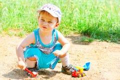 与玩具的儿童游戏在沙子 库存照片