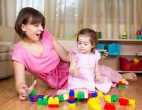 与玩具的妈妈和孩子戏剧在家 免版税库存照片