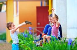 与玩具的孩子开枪使用在战争,五颜六色室外中 免版税图库摄影