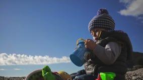 与玩具的小儿童游戏在冬天衣裳和帽子的海岸 影视素材